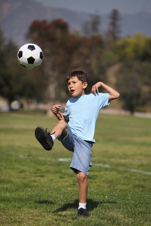boy ball: A young boy kicks a soccer ball in a park setting
