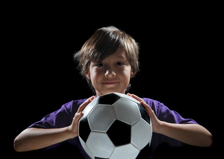 Dramatic back-lit boy with soccer ball on black background Stock Photo
