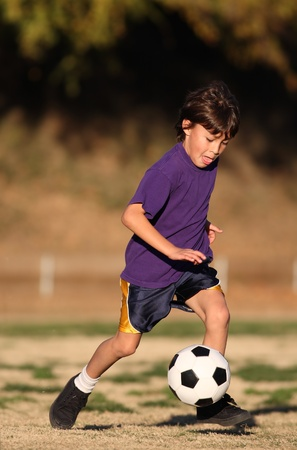 Boy in purple shirt plays soccer in the late afternoon sunlight  Stock Photo