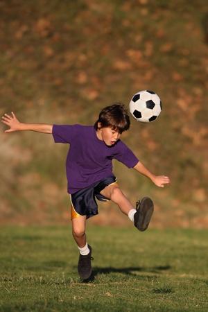 Jongen schopt een voetbal in de vroege avond zon.