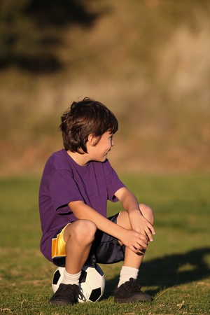 Boy sits on soccer ball looking to side in late afternoon sun - with copy space above photo