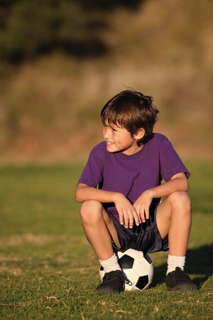 Boy sits on soccer ball looking to side in late afternoon
