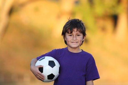 Portrait of young boy with soccer ball at sunset with beautiful gold fall foliage blurred background and copy space to left  photo