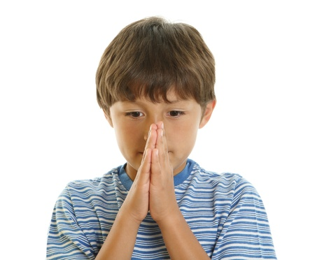 anticipating: Young boy looking upwards with hands together - praying or waiting in anticipation