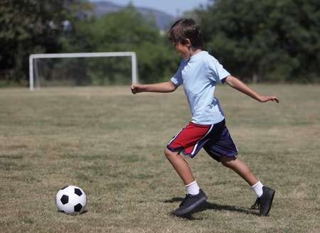 Young boy preparing to kick a soccer ball with goal in the background photo