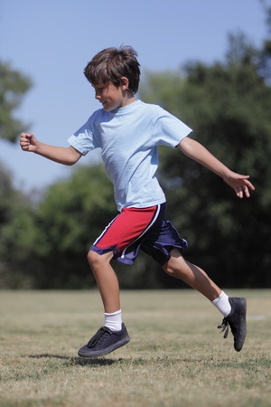 A young boy runs happily in a field