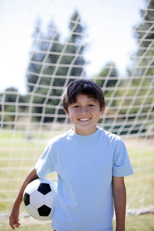 Backlit boy with Soccer ball with goal behind and blurred background providing copy space above photo