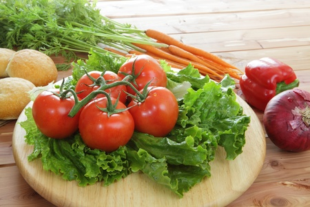Fresh organic tomatoes on the vine with red onion, garlic, lettuce, carrots, and red pepper with dinner rolls in a rustic setting Stock Photo