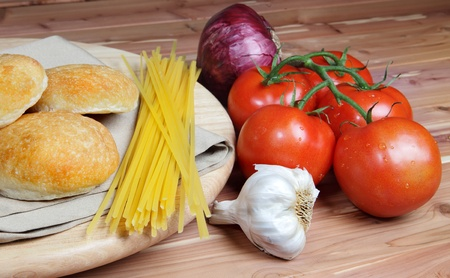 Italian style ingredients including tomatoes, uncooked linguini, onion and garlic with dinner rolls on a wood background Stock Photo - 14020316