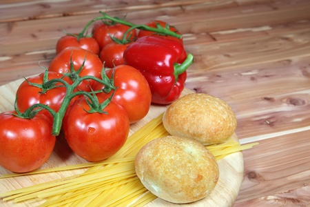 Italian style ingredients including tomatoes, uncooked linguini, onion and garlic with dinner rolls on a wood background - with copy space right Stock Photo - 14020333