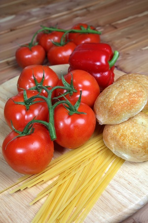 Italian style ingredients including tomatoes, uncooked linguini, onion and garlic with dinner rolls on a wood background - with copy space right Stock Photo - 14020340