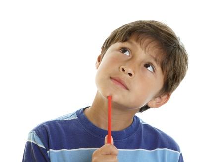 niños pensando: Muchacho joven mira pensativo con leve sonrisa y miradas hacia arriba mientras sostiene un lápiz - sobre fondo blanco Foto de archivo