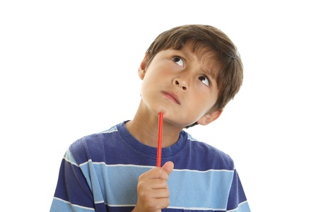 Young boy looks thoughtful and gazes upwards while holding a pencil - on white background photo
