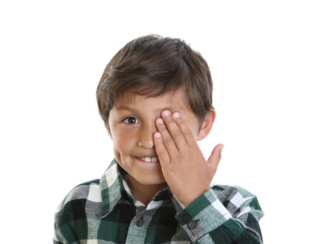 Happy smiling young boy covers one eye with his hand - on white background photo