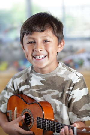 A happy smiling young boy plays his guitar or ukulele