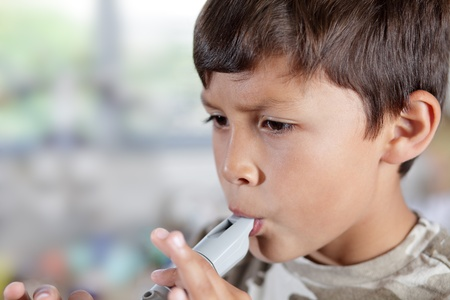 A young boy plays a recorder with concentration - shallow depth of field with copy space to left Stock Photo