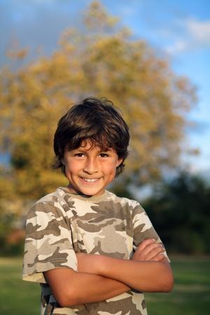 niños latinos: Feliz sonriente muchacho en el parque cerca de la puesta del sol con poca profundidad de campo y espacio de la copia en la parte superior