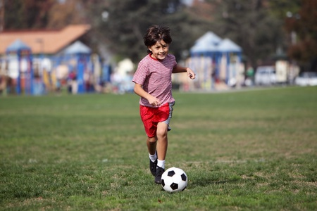 Boy playing soccer in the park - authentic action - horizontal with copy space