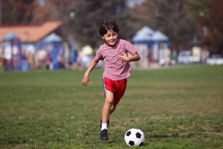kids activities: Boy playing soccer in the park - running towards camera - copy space left and right