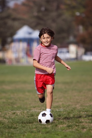 Boy playing soccer in the park - running towards camera - copy space top - portrait format