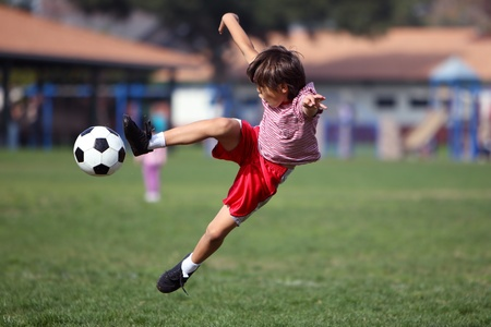 kids activities: Boy playing soccer in the park - authentic action - horizontal with copy space
