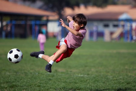 boy feet: Boy playing soccer in the park leaps up to get the ball - authentic action - copy space