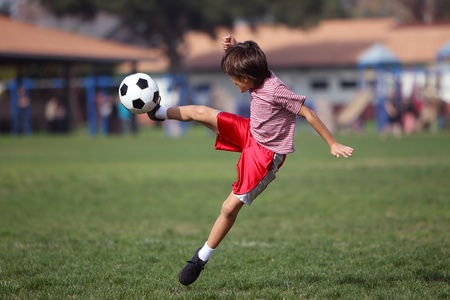 kids feet: Boy playing soccer in the park - Authentic action - copy space
