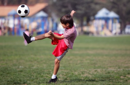 Boy playing soccer in the park - Authentic action - copy space