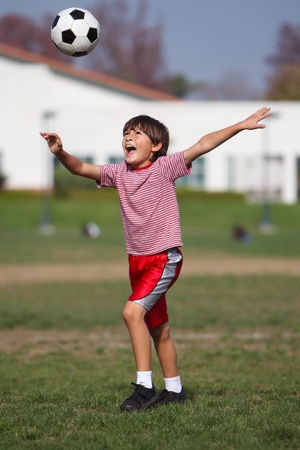 Boy playing soccer in the park - Authentic action - vertical portrait format Stock Photo