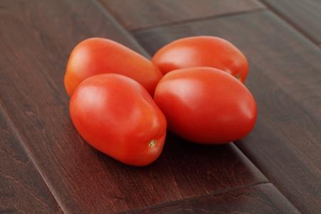 Fresh organic roma plum tomatoes on a rustic dark wood surface