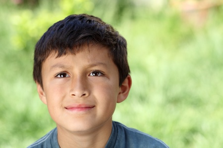 Young boy outisde looking up with natural green background - copy space to right