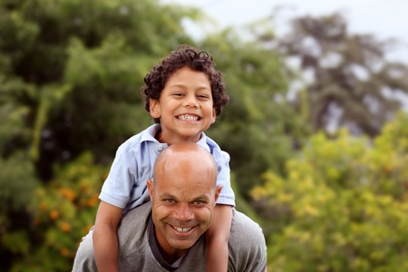 Mixed race father and son playing in the back garden