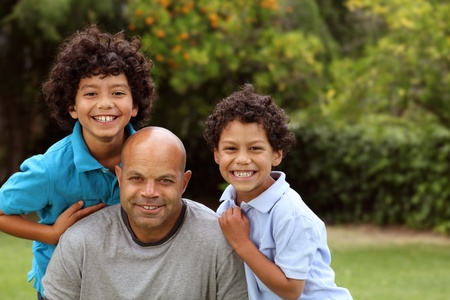 Mixed race father and sons playing outside Stock Photo