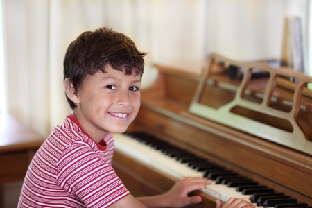 Youngboy smiles while playing the piano
