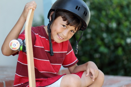 Young skateboarder rests wearing helmet and red teeshirt - shallow depth of field Stock Photo