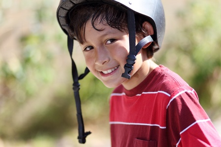 Young skateboarder smiles at the camera outside with natural green background - shallow depth of field Stock Photo