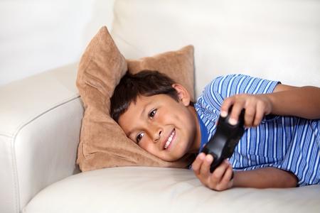 niños jugando videojuegos: Niño jugando juegos de computadora mientras relxing en el sofá