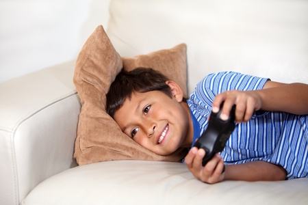 kids playing video games: Young boy playing computer game while relxing on the sofa Stock Photo
