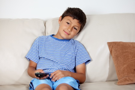 Young boy watching TV with remote control