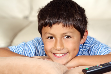 Young boy watching TV with remote control photo