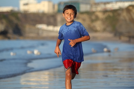 Young boy plays and runs in the surf along an English beach near sunset photo