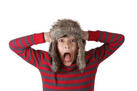 Boy in furry hat puloling funny faces on white background Stock Photo