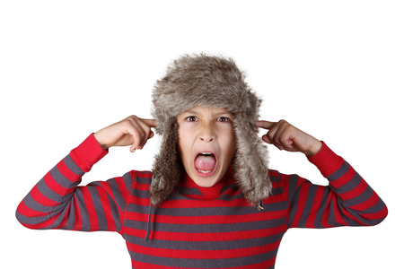 Boy in furry hat puloling funny faces on white background photo