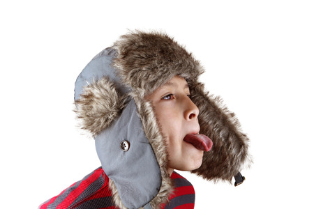 acting: Boy in furry hat puloling funny faces on white background Stock Photo