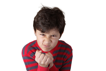 scowling: Mad angry boy with clenched fists on white isolated background