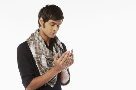 kameez: Man in traditional clothing praying
