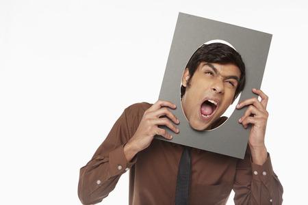 making faces: Imprenditore in possesso di un taglio fuori di cartone con foro, rendendo le facce