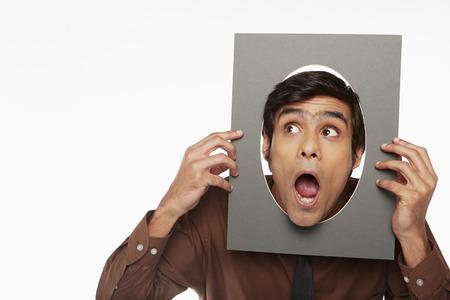making faces: Imprenditore in possesso di un cartone ritagliato con foro, facendo facce
