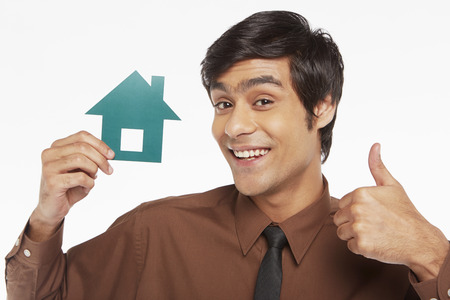 Cheerful businessman holding up a cut out house photo