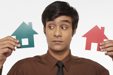 Businessman holding up two cut out houses, contemplating Stock Photo - 22635810